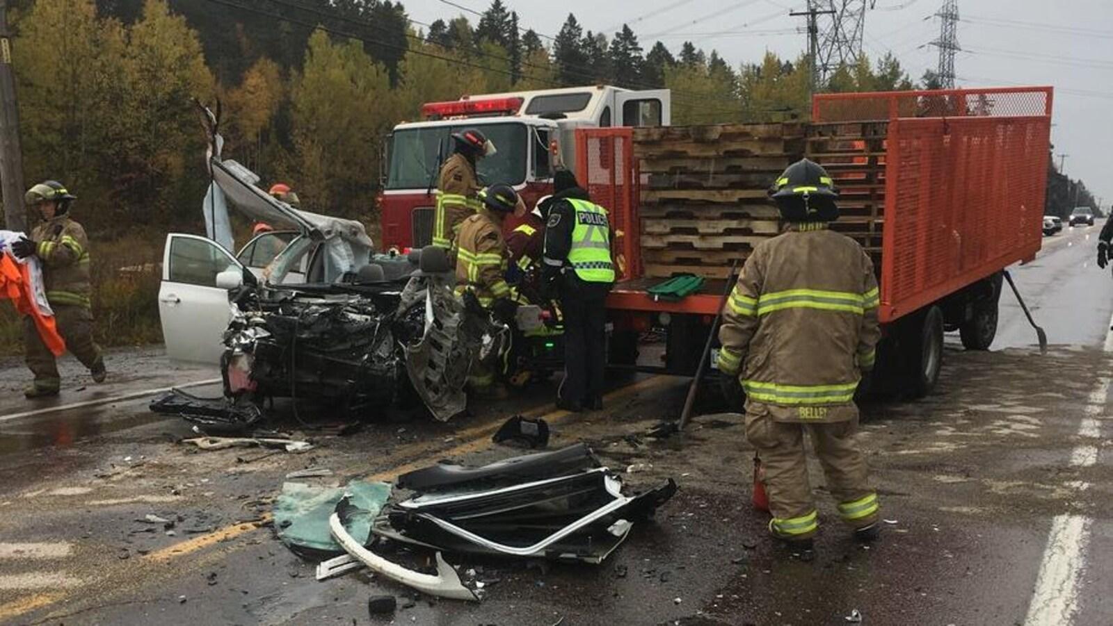 Des pompiers s'affairent autour du véhicule accidenté.