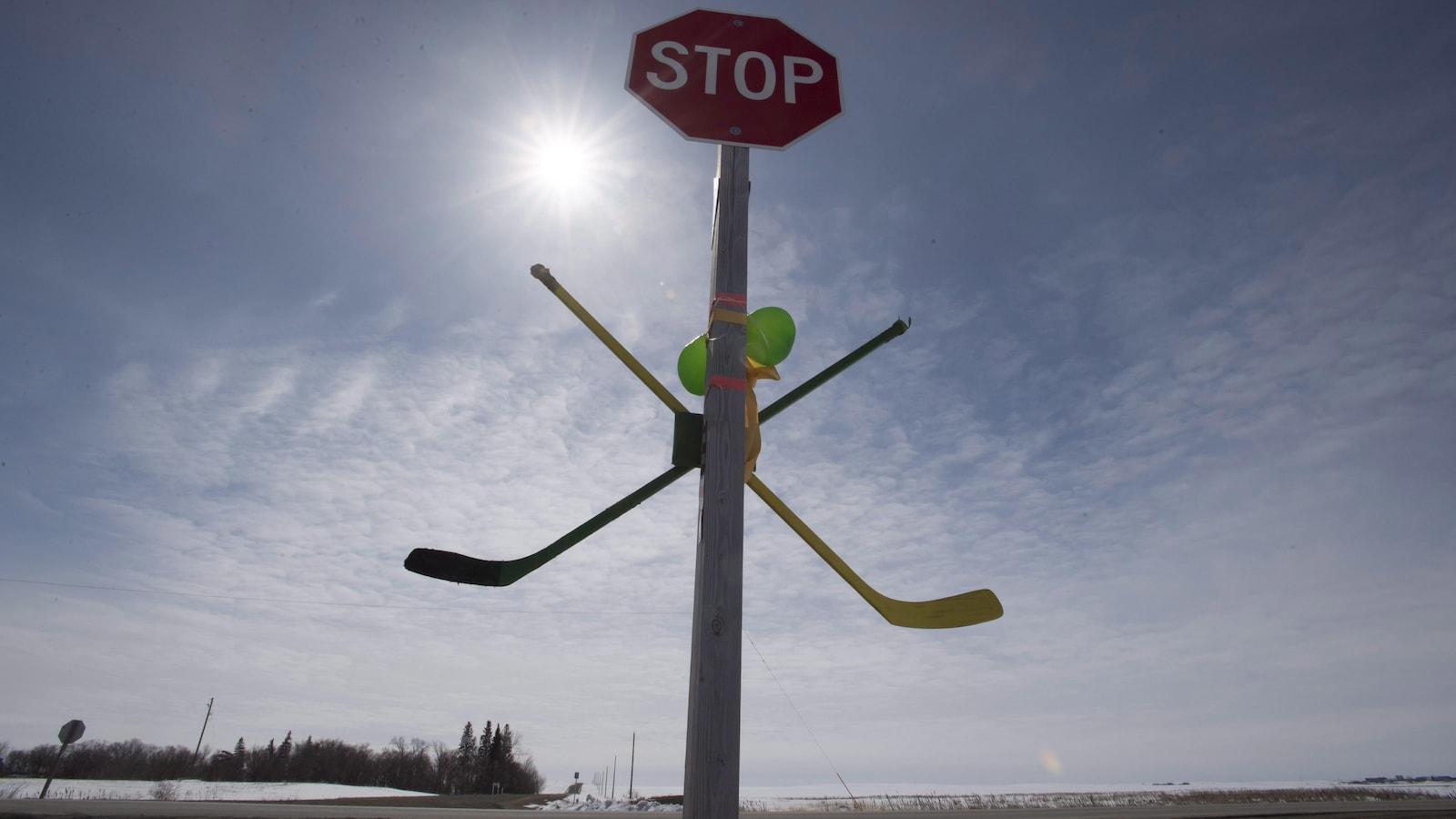 Une paire de hockey est attachée à un panneau d'arrêt en hommage aux Broncos de Humboldt.