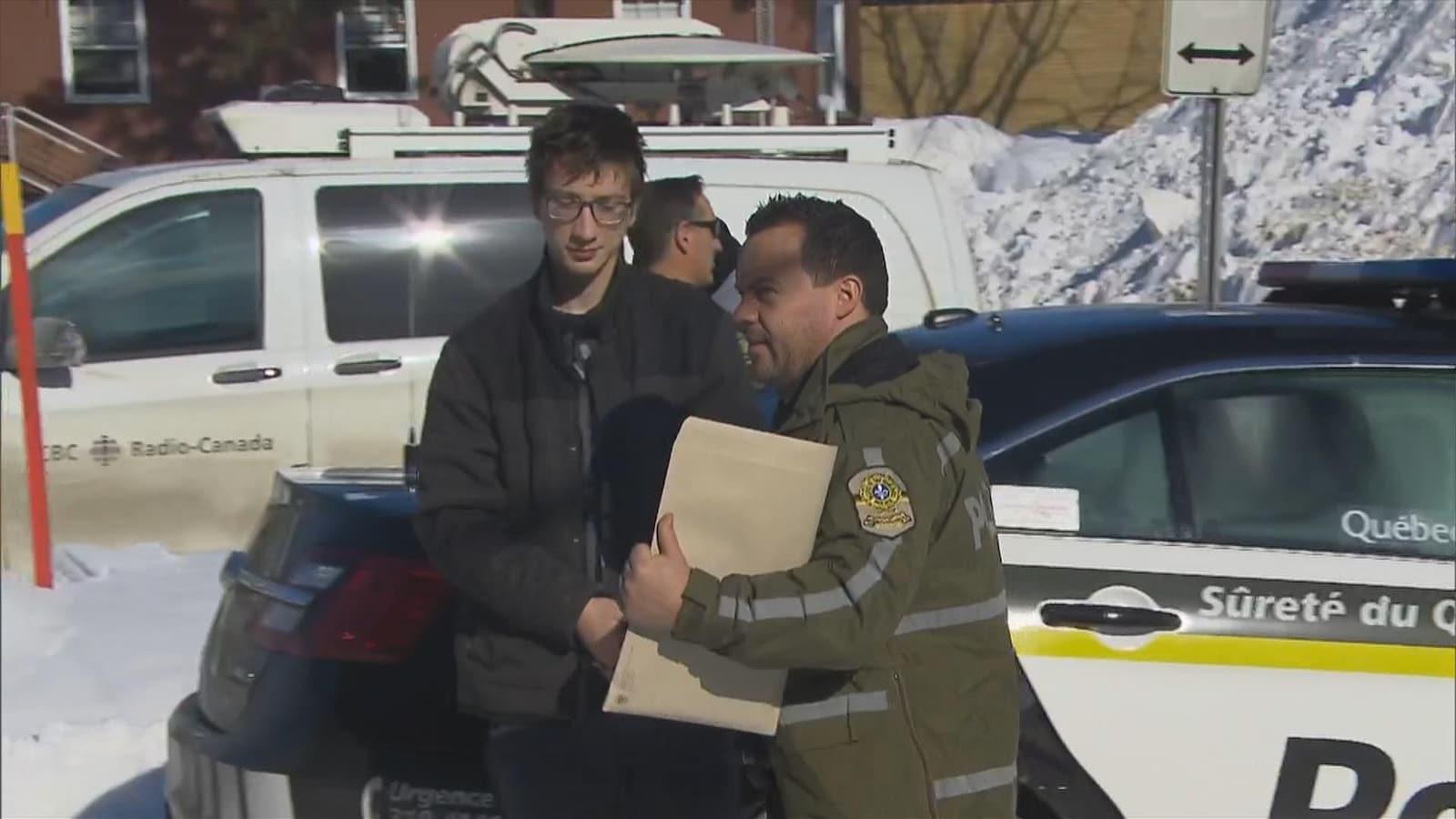 Un jeune homme est menotté et il est accompagné d'un policier de la Sûreté du Québec.