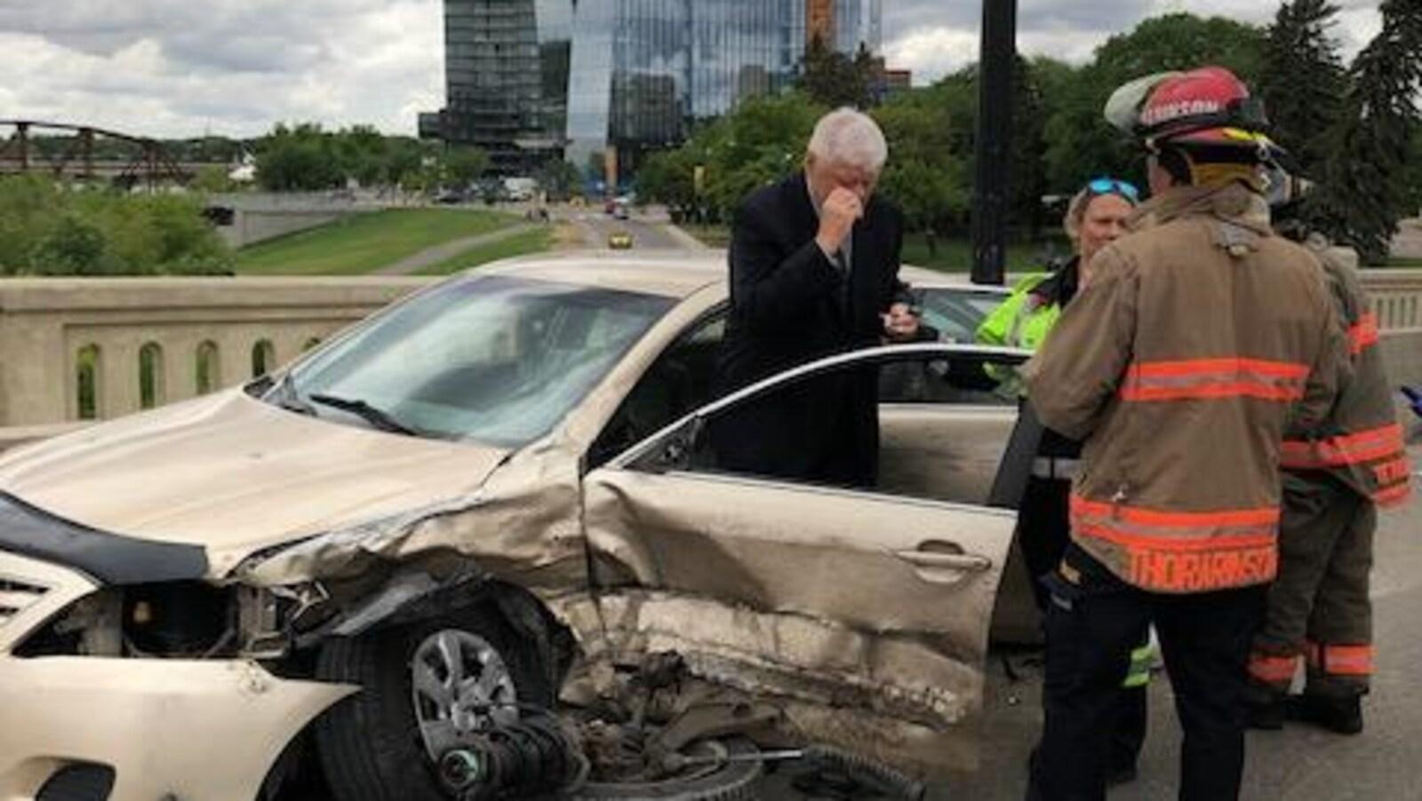 Un passager et des premiers répondants debout devant la voiture endommagée par l'accident.