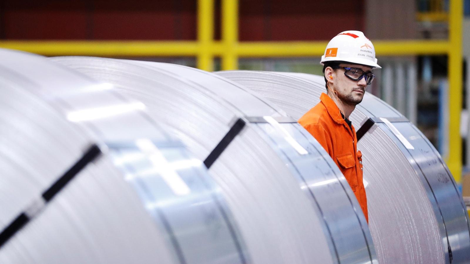 Un travailleur se tient debout entre des rouleaux de feuilles d'acier.