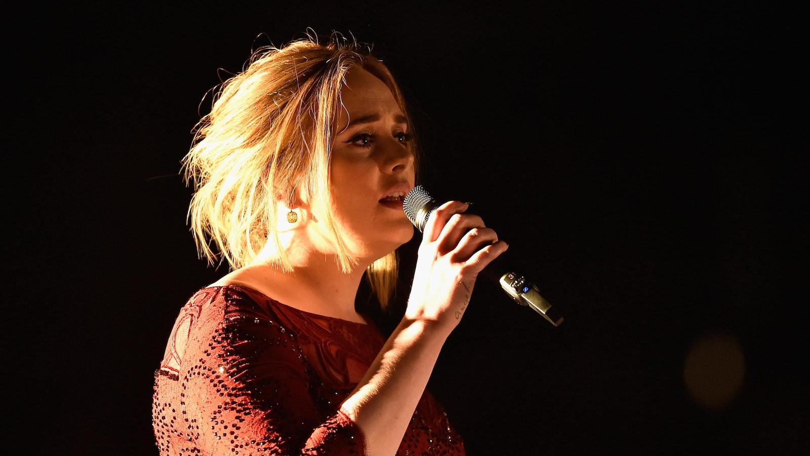 La chanteuse Adele chante sur scène vêtue d'une robe rouge lors de la cérémonie de remise des prix Grammy en 2016.