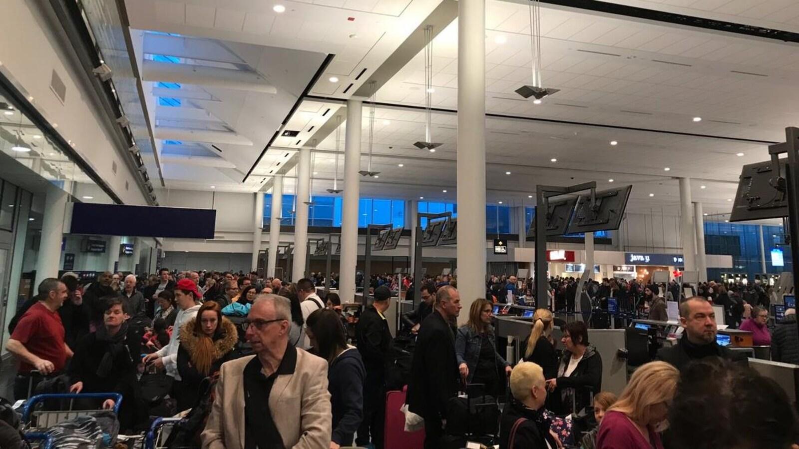 Plusieurs personnes attendent de pouvoir enregistrer leurs bagages à l'aéroport de Montréal.