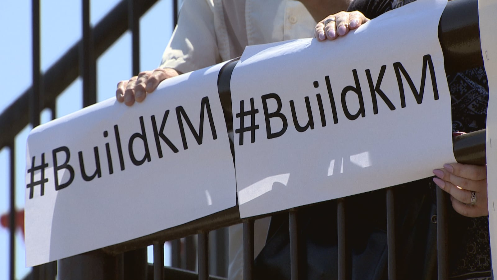 Deux affiches sur lesquelles il est inscrit # Build KM, tenues par des manifestants, à Calgary.