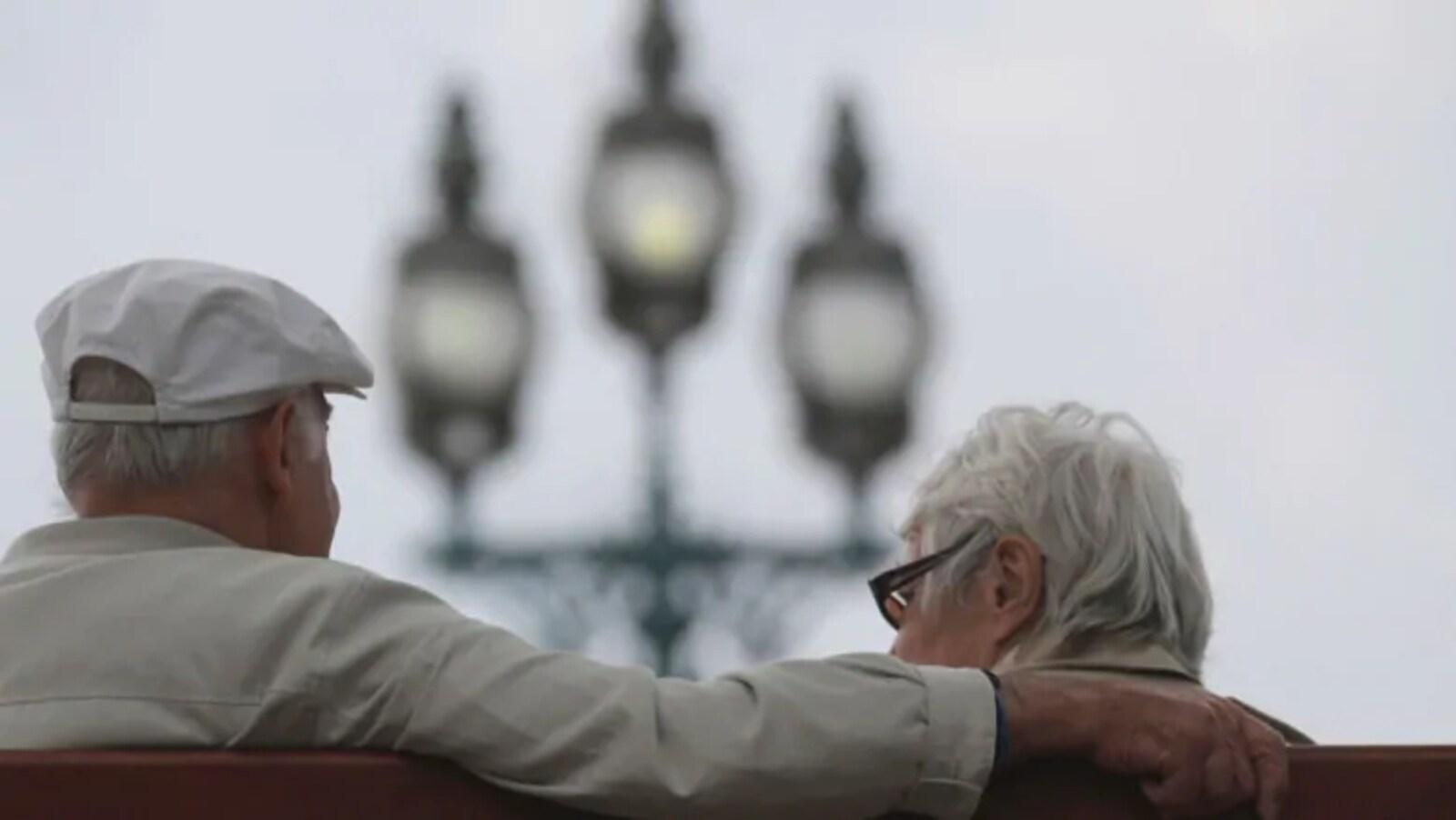 Deux aînés, de dos, assis sur un banc.