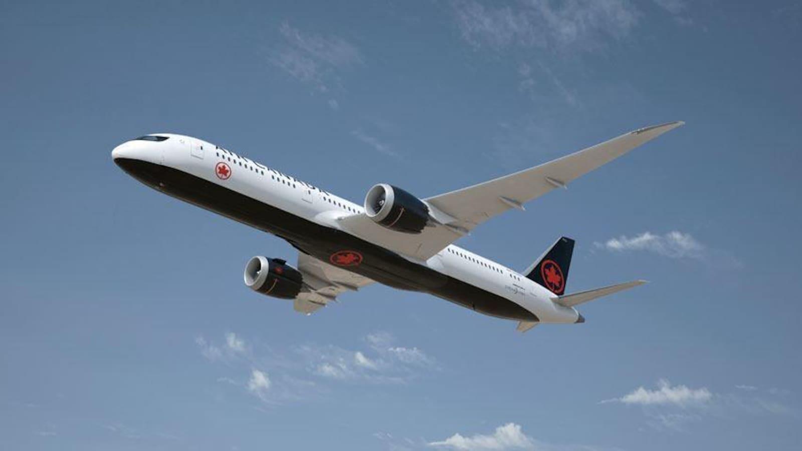 Un avion peint aux couleurs d'Air Canada (noir et rouge) en plein vol.