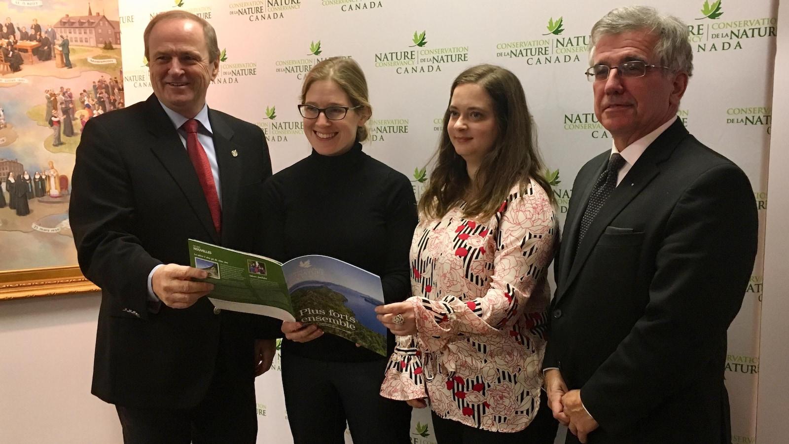 Le député fédéral Robert Morrissey et le ministre provincial de l'Environnement, Richard Brown, entourent Julie Vasseur de l'organisme Conservation de la nature Canada et Rachel Lapointe du Musée acadien de l'Île-du-Prince-Édouard.