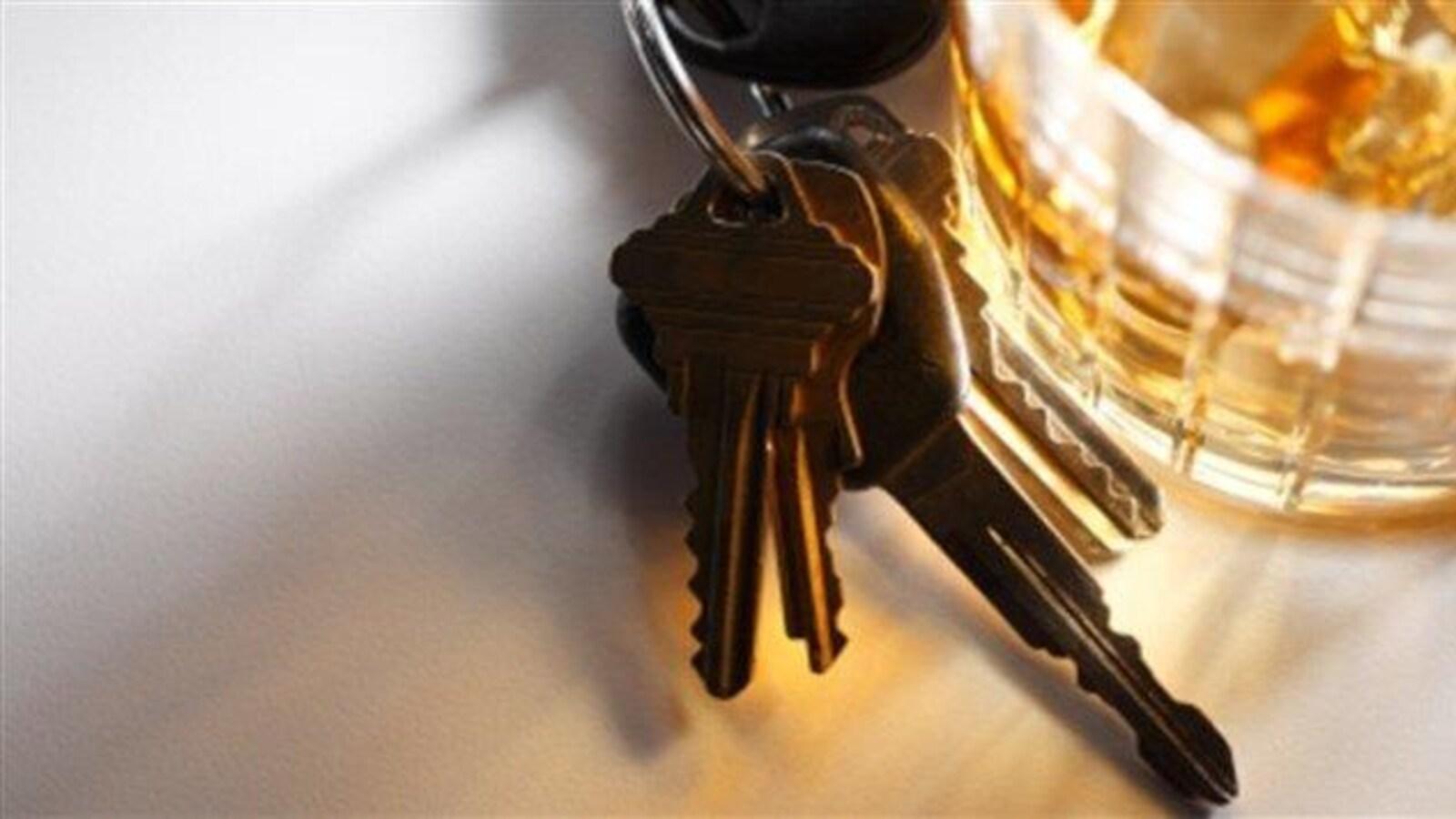 Des clés de voiture à côté d'un verre d'alcool.