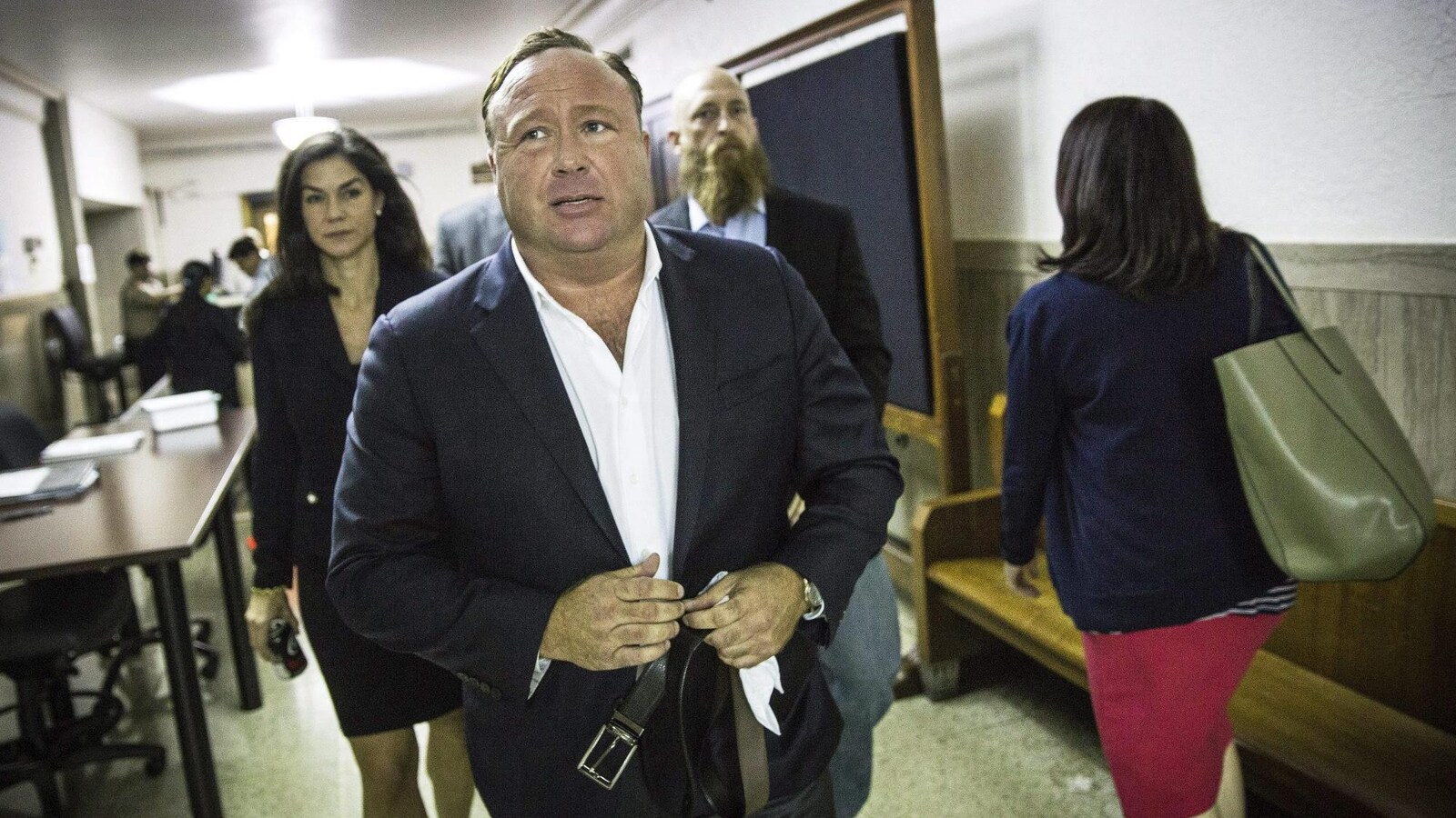 Alex Jones marche dans un corridor.