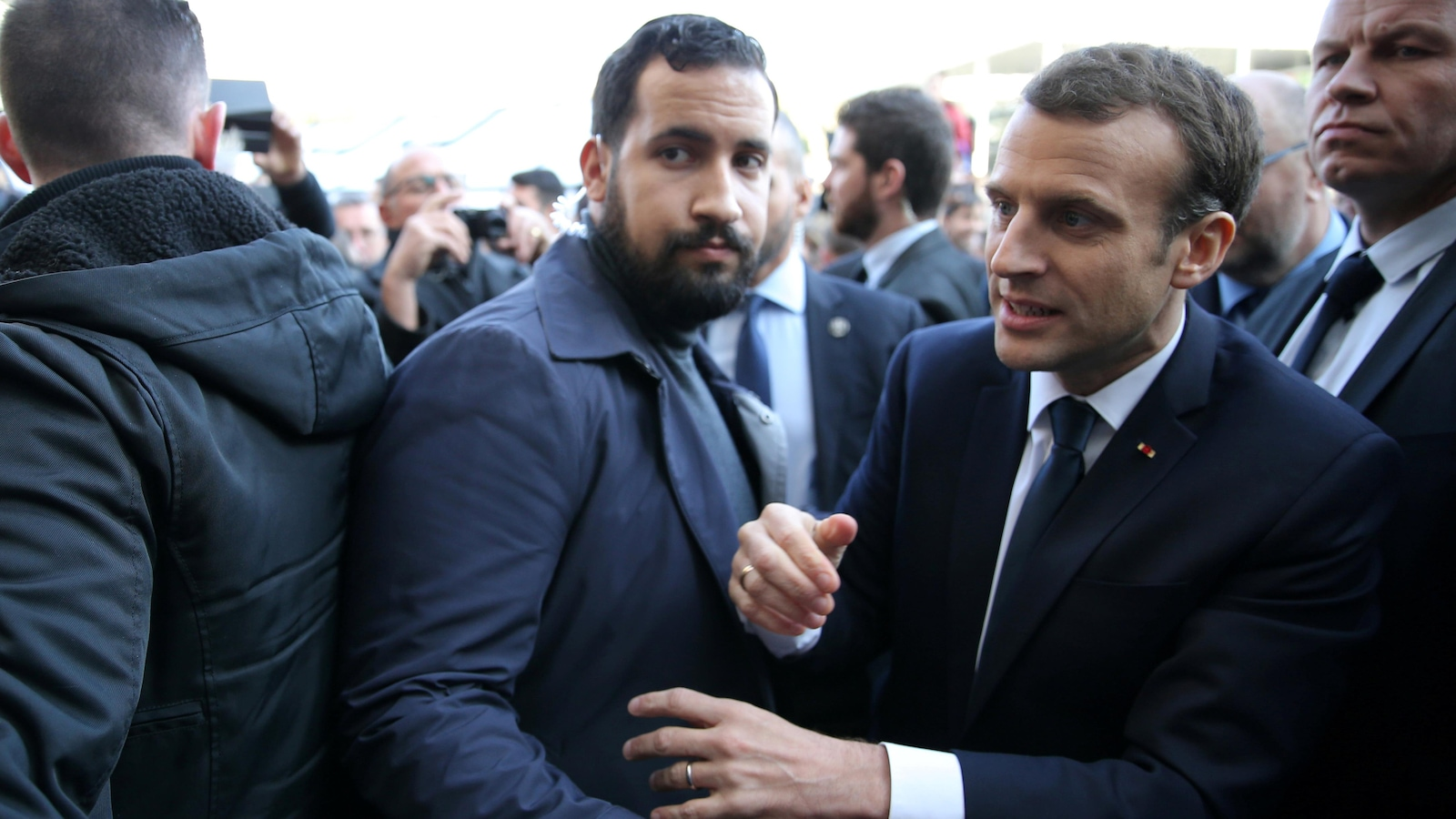 Alexandre Benalla met son bras devant Emmanuel Macron.