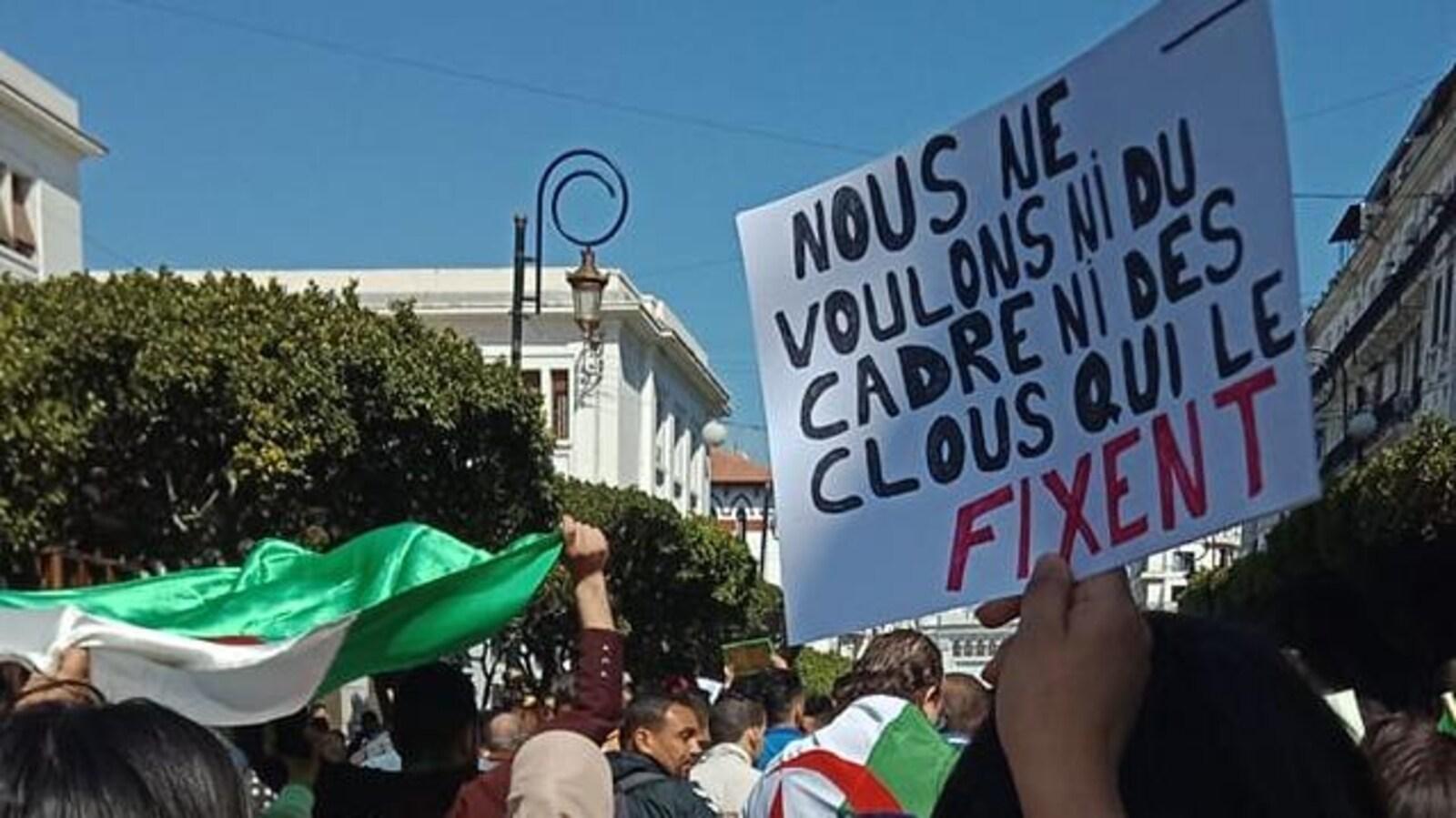 Un manifestant tient une pancarte sur laquelle on peut lire : « Nous ne voulons ni du cadre ni des clous qui le fixent ».