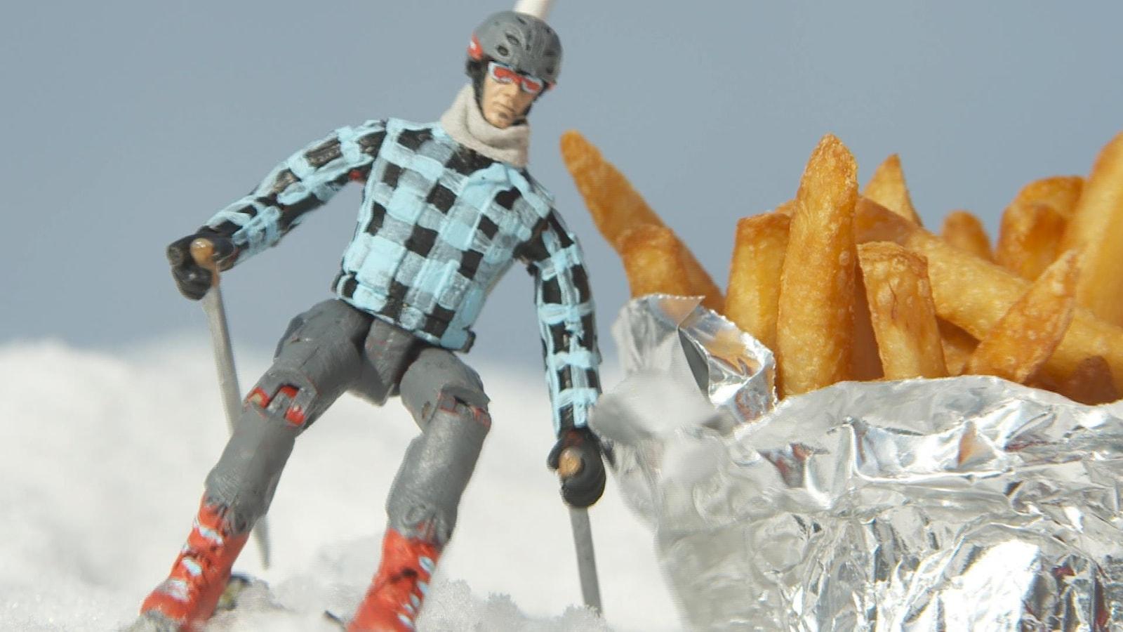 Un personnage en plastique ski près d'un sac de frites