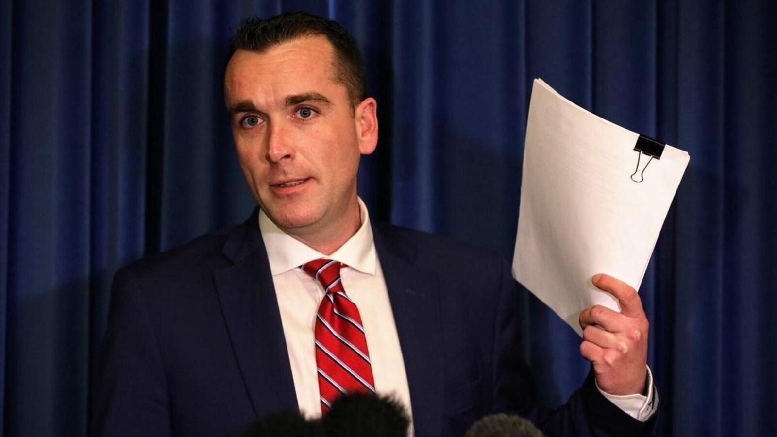 Alan Mullen est en costume cravate avec dans sa main gauche une copie du rapport.