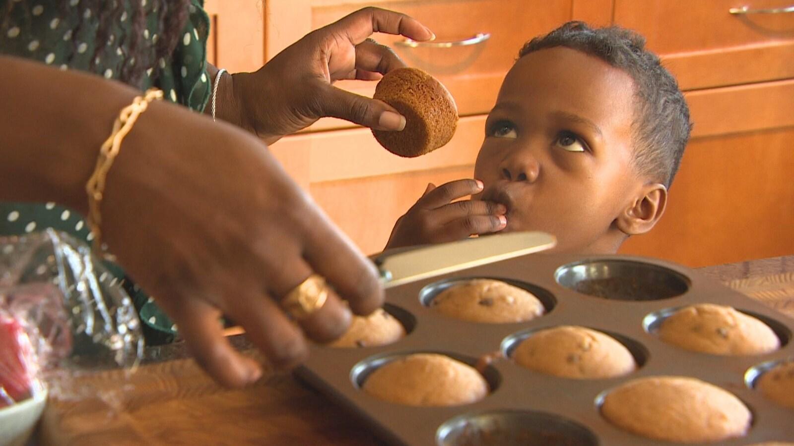 Un jeune garçon se lèche les doigts tandis que sa mère lui tend un muffin sorti du four.