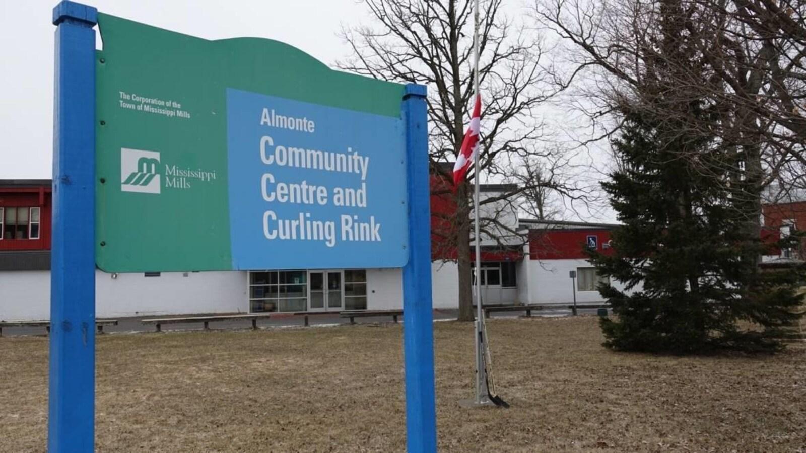 En avant-plan, un panneau sur lequel on peut lire « Almonte Community Centre and Curling Rink ». En arrière-plan, un drapeau canadien en berne avec deux bâtons de hockey.