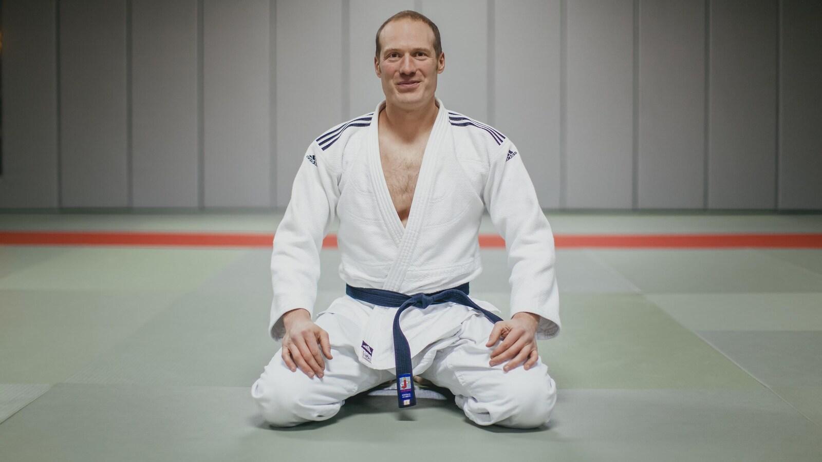 Un homme dans un habit d'art martial est à genoux dans un gymnase.