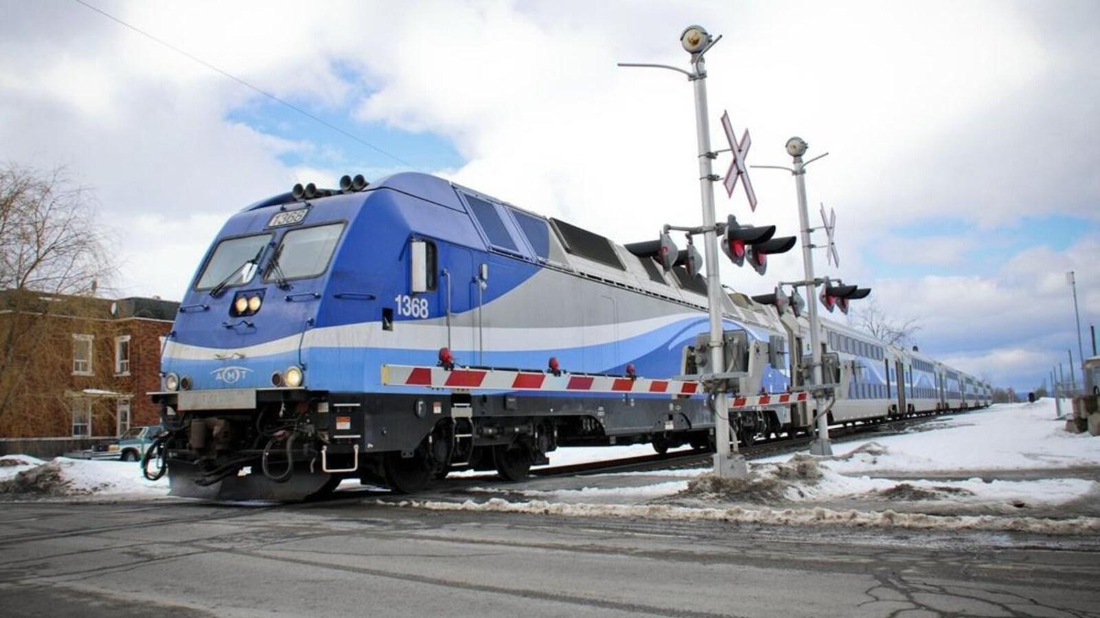 Un train de banlieue d'Exo traverse un passage à niveau, en hiver.