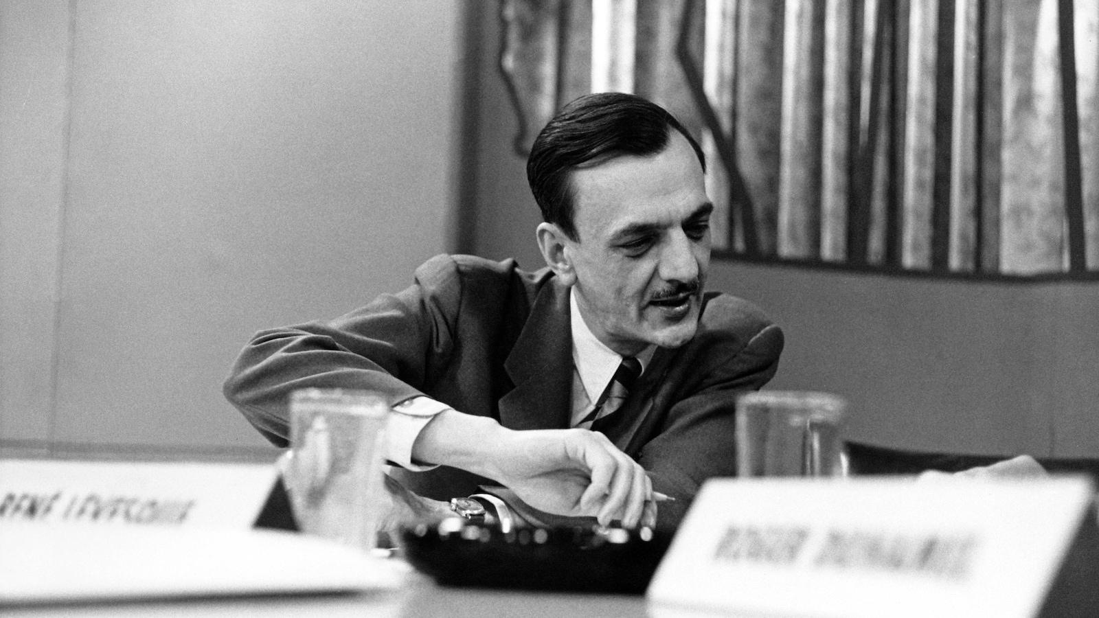 André Laurendeau, crayon à la main, regarde les résultats de l'élection fédérale de 1958.