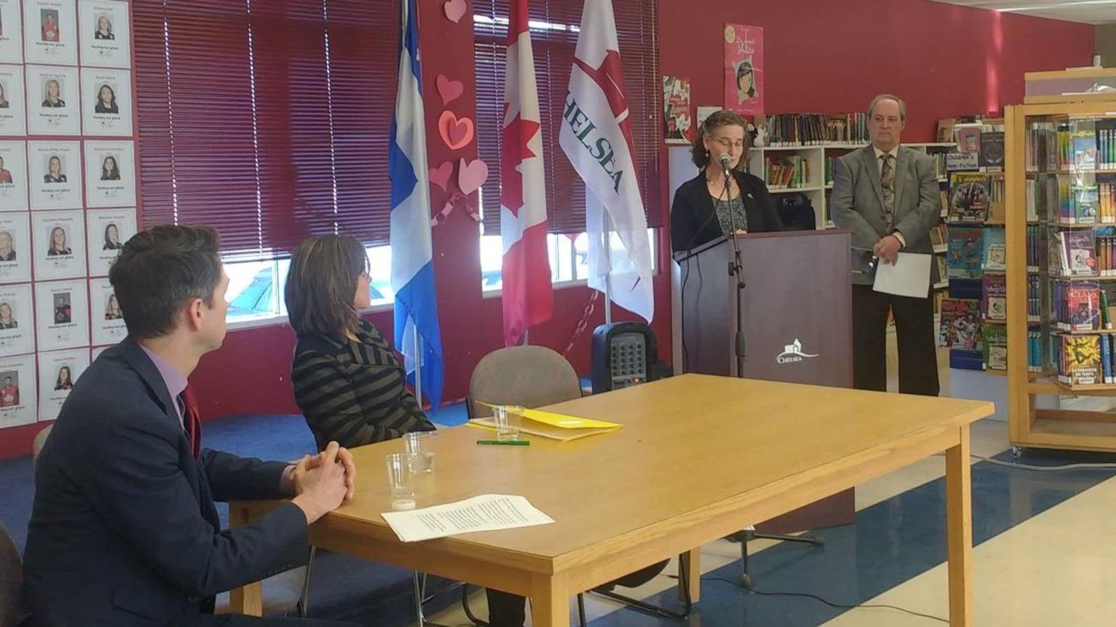 La mairesse est à un podium alors que la ministre responsable de la région à Québec Stéphanie Vallée et le député fédéral de Pontiac Will Amos sont assis à une table