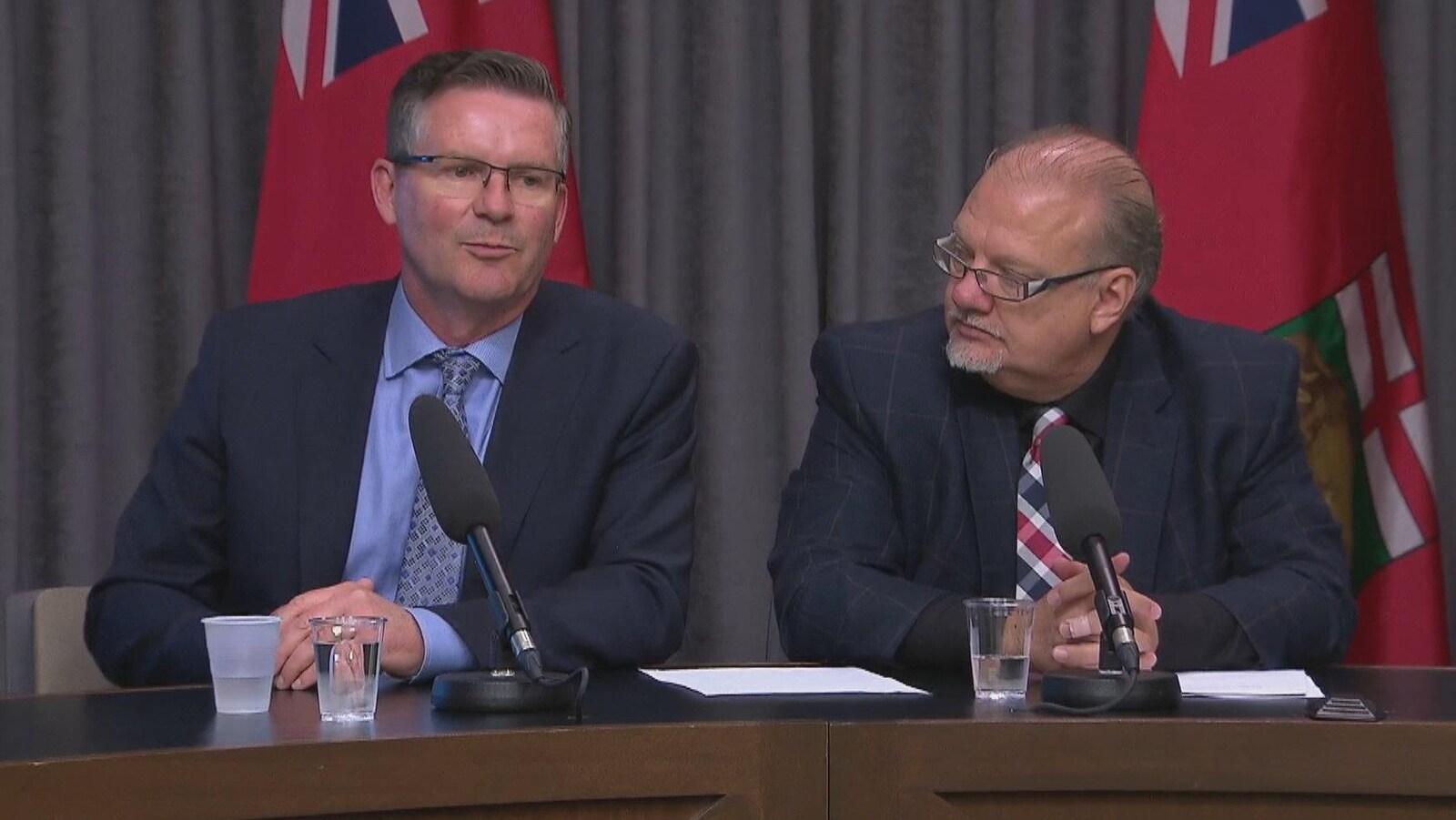 Deux hommes en complet sont assis à une table devant des drapeaux manitobains et ont des microphones devant eux.