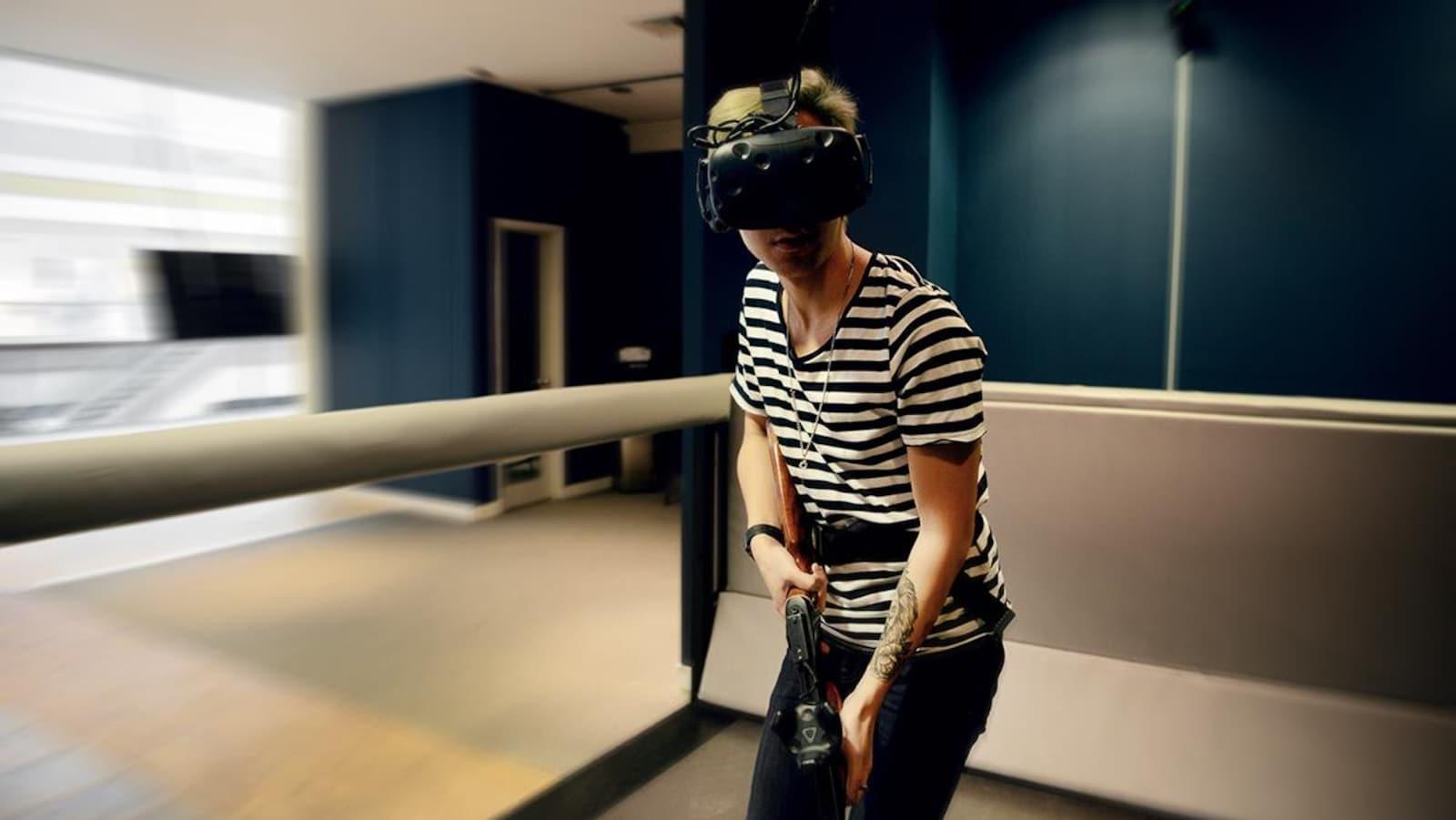 Un joueur armé d'un fusil de plastique et équipé d'un masque de réalité virtuelle joue sur le tapis roulant.