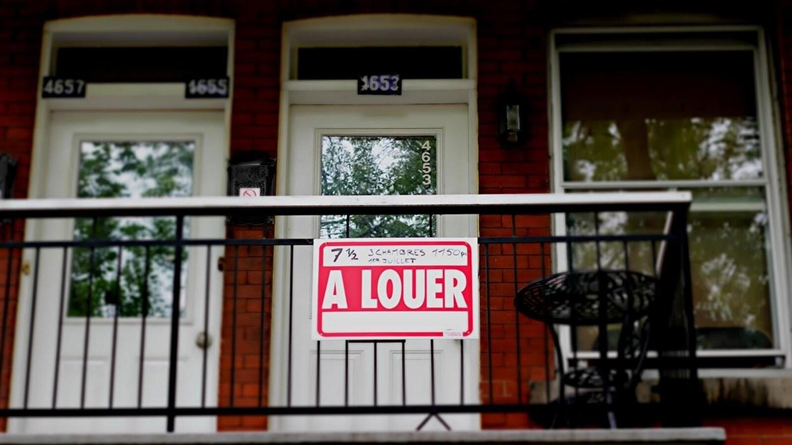 Un immeuble d'appartements à Montréal avec une pancarte À louer devant l'une des portes.