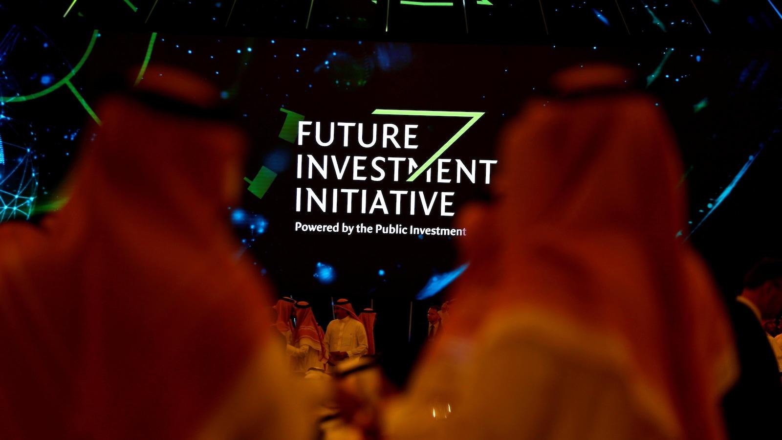 Des participants regroupés autour d'un panneau vantant un fonds d'investissement saoudien