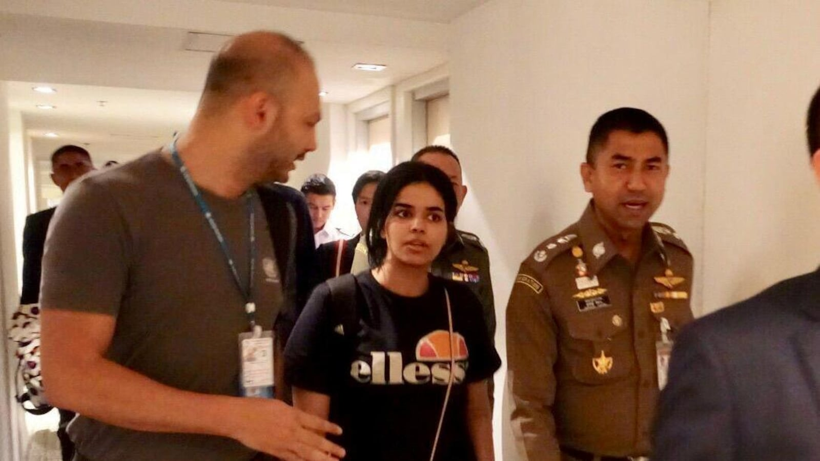 Une jeune femme circule dans un corridor, entourée de responsables et d'officiers en uniforme.