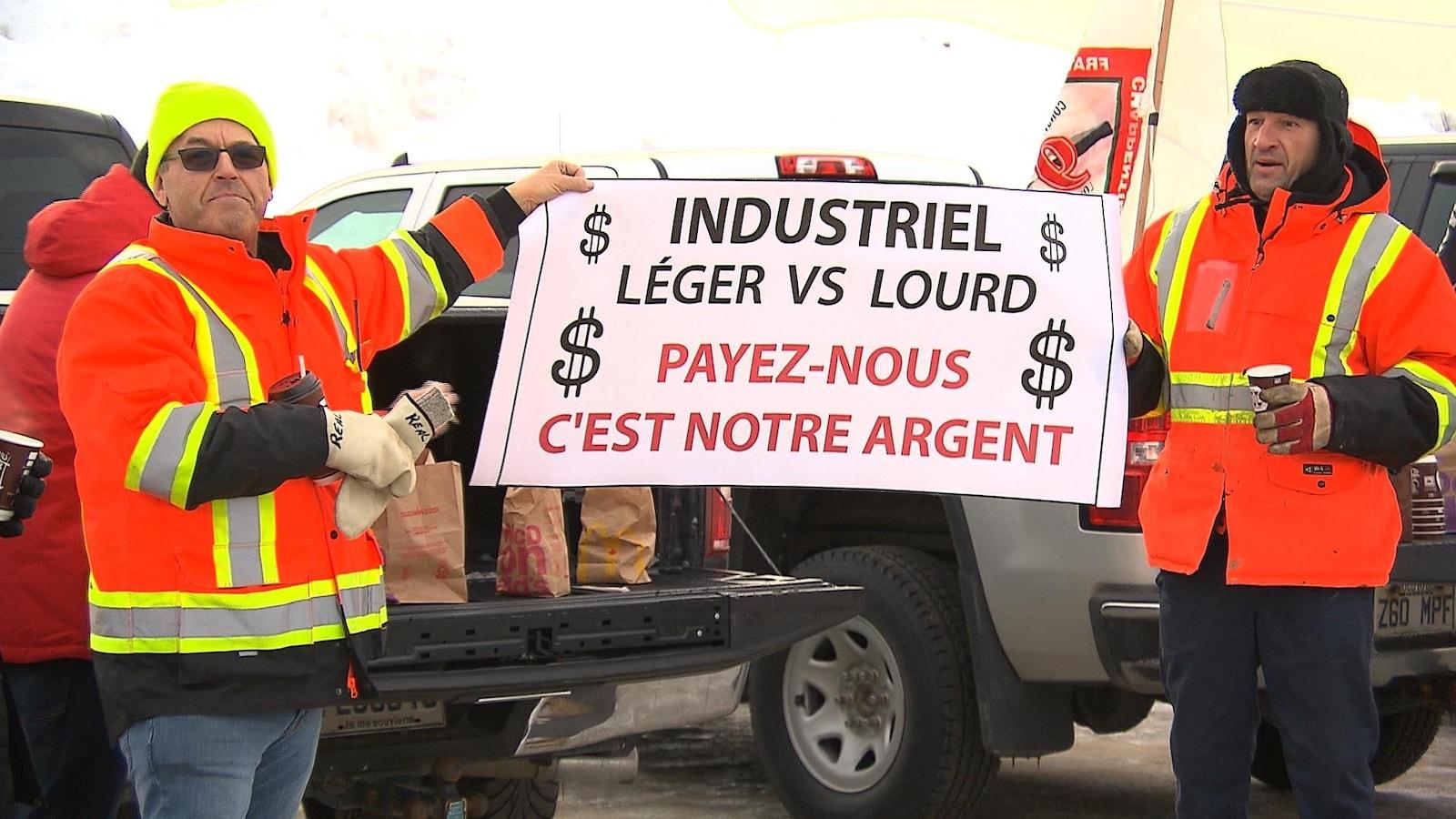 Deux manifestants brandissant une pancarte : « Payez-nous c'est notre argent »