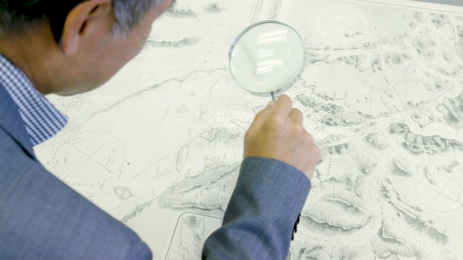 Un homme lit une carte topographique à l'aide d'une loupe.