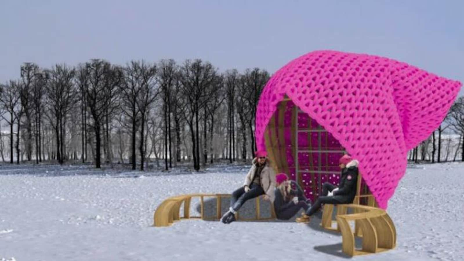 Un homme et deux femmes assis sur un banc en bois près du lac protégés par une énorme tuque rose.