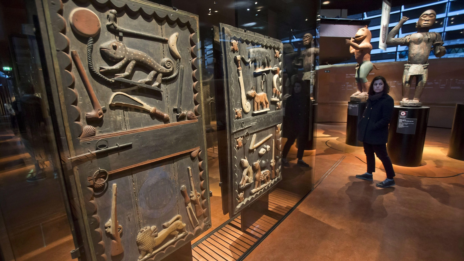 A visitor walks past a door of the king's palace Gele of the Dahomey kingdom, dated19th century, today's Benin, at Quai Branly museum in Paris, France, Friday, Nov. 23, 2018. From Senegal to Ethiopia, artists, governments and museums are eagerly awaiting a report commissioned by French President Emmanuel Macron on how former colonizers can return African art to Africa.(AP Photo/Michel Euler)
