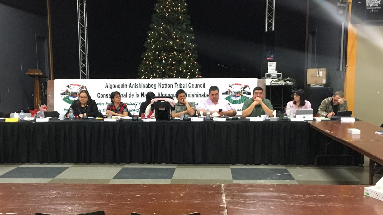 Des chefs algonquins sont assis derrière une longue table dans une salle communautaire.