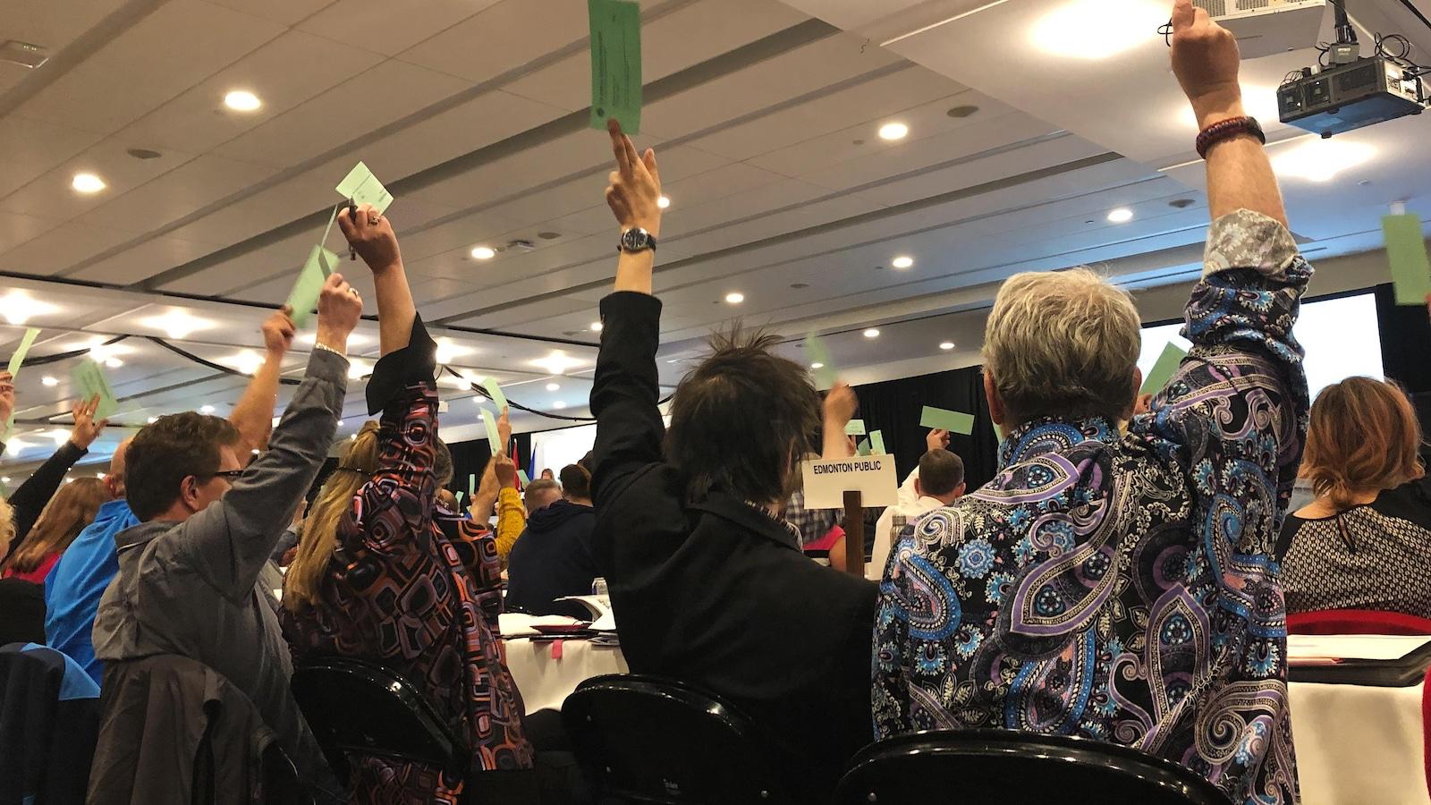 Des délégués brandissent leur bulletin de vote pour voter en faveur de la résolution.