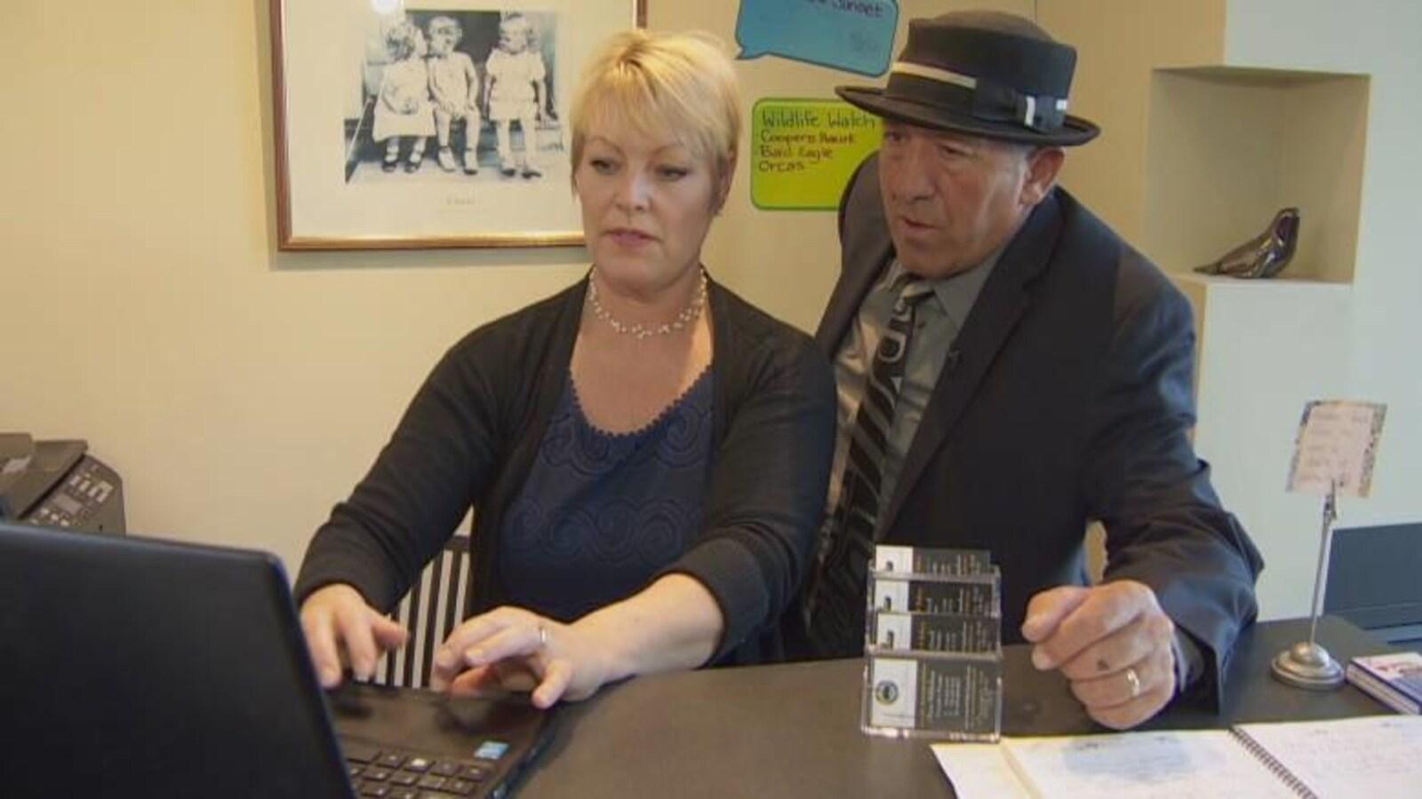 Un couple regarde un écran d'ordinateur à la réception d'un hôtel.
