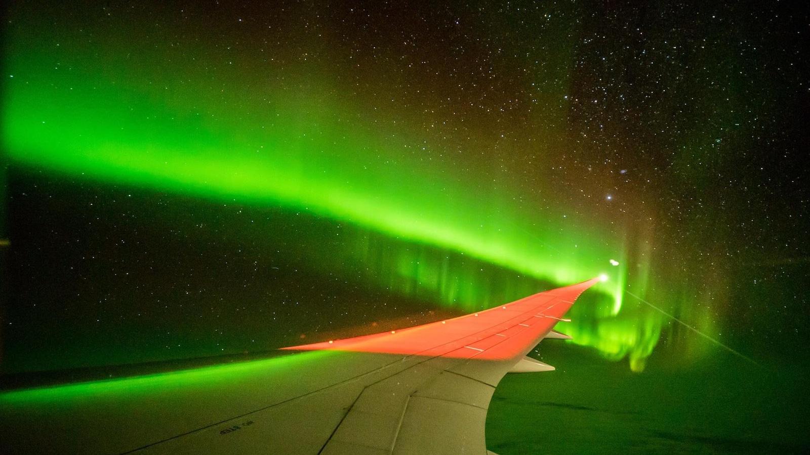 aurores australes aperçues au bout de l'aile d'un avion