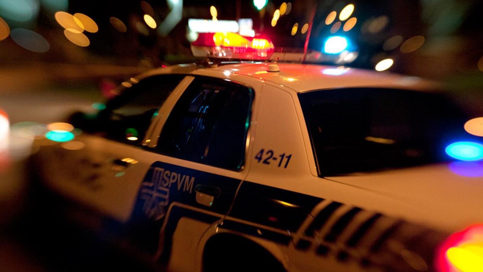 Zoom sur une autopatrouille du Service de police de Montréal dans la nuit, en été. Modèle désuet de Ford Crown Victoria.