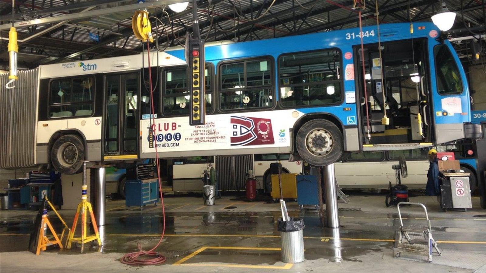 Un autobus en réparation dans un garage de la STM.