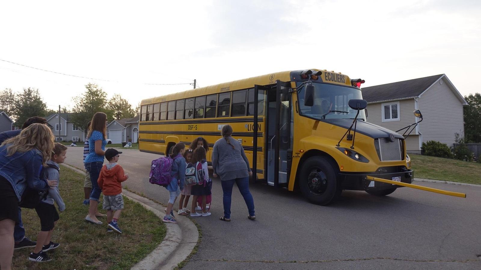 Des enfants qui embarquent dans l'autobus scolaire électrique.