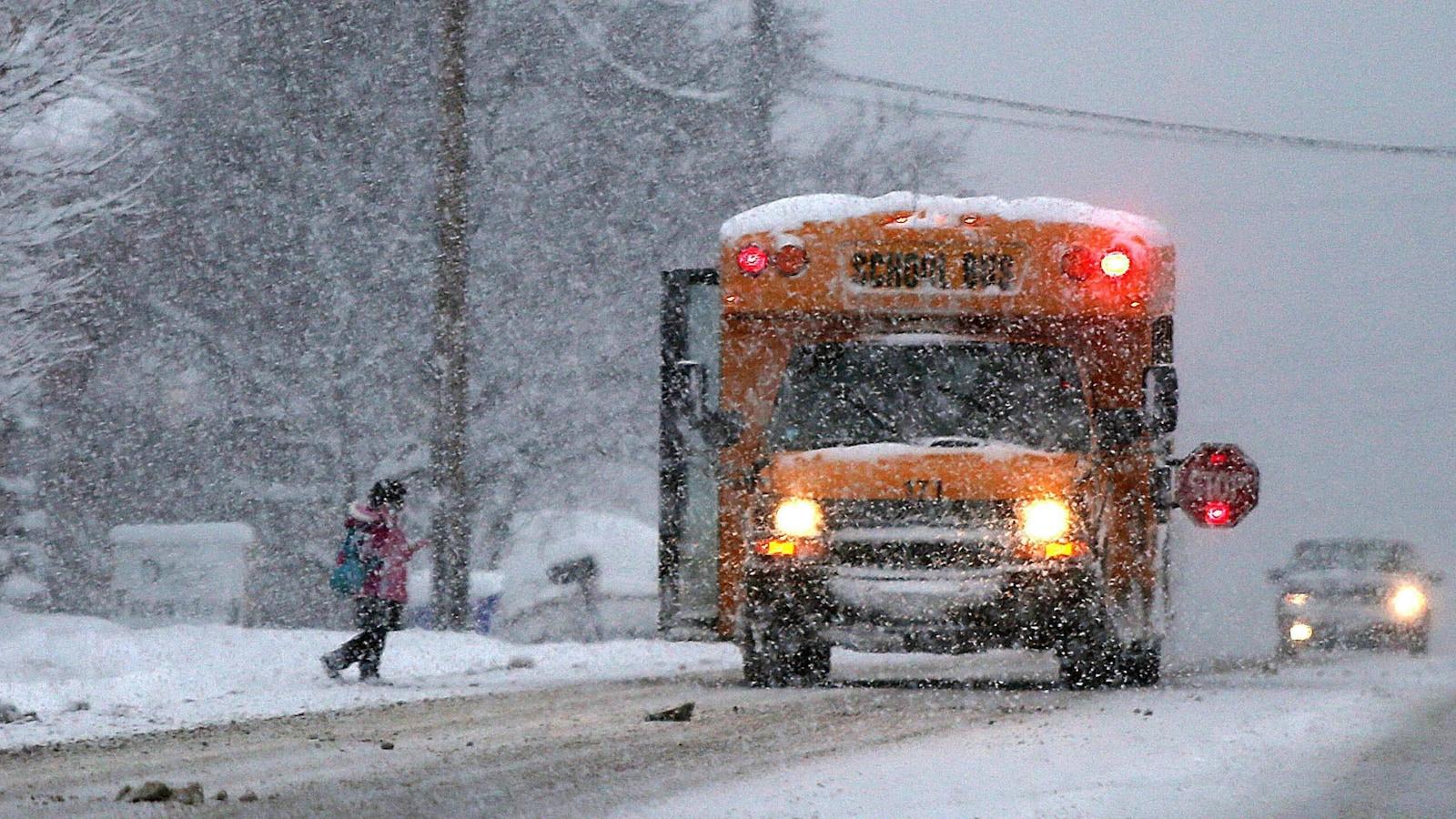Une petite fille se dirige vers son autobus scolaire en pleine tempête de neige.
