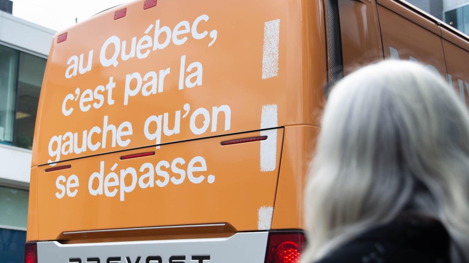 Un autobus orange. On y lit «Au Québec, c'est par la gauche qu'on se dépasse». On y voit la co-porte-parole de Québec Solidaire, Manon Massé, de dos.