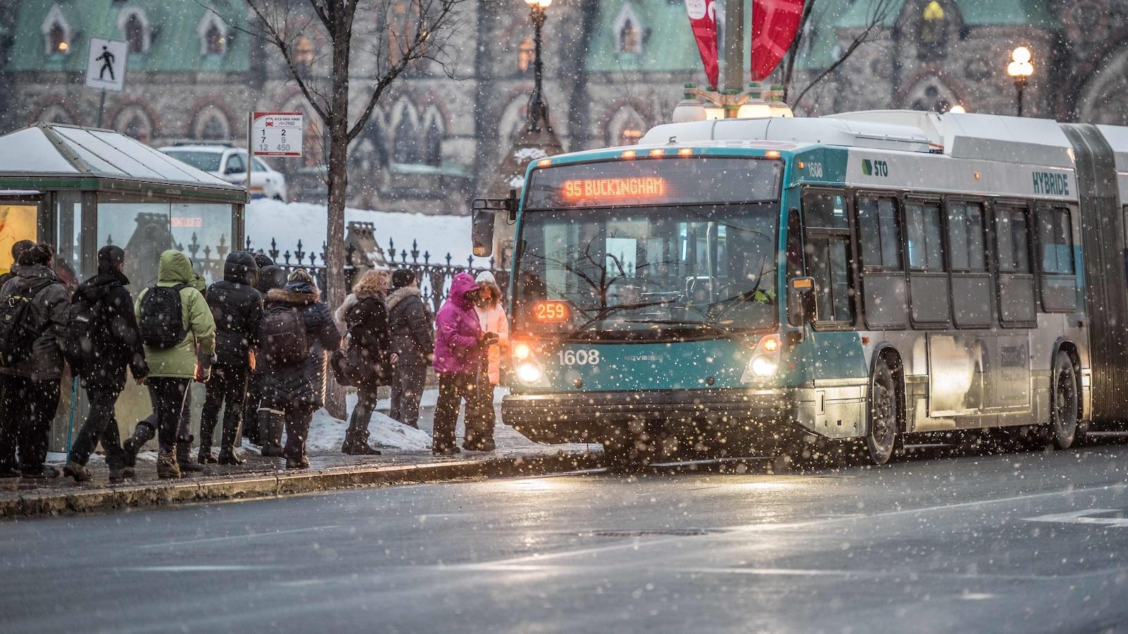 Des citoyens attendent un autobus de la Société de transport de l'Outaouais.