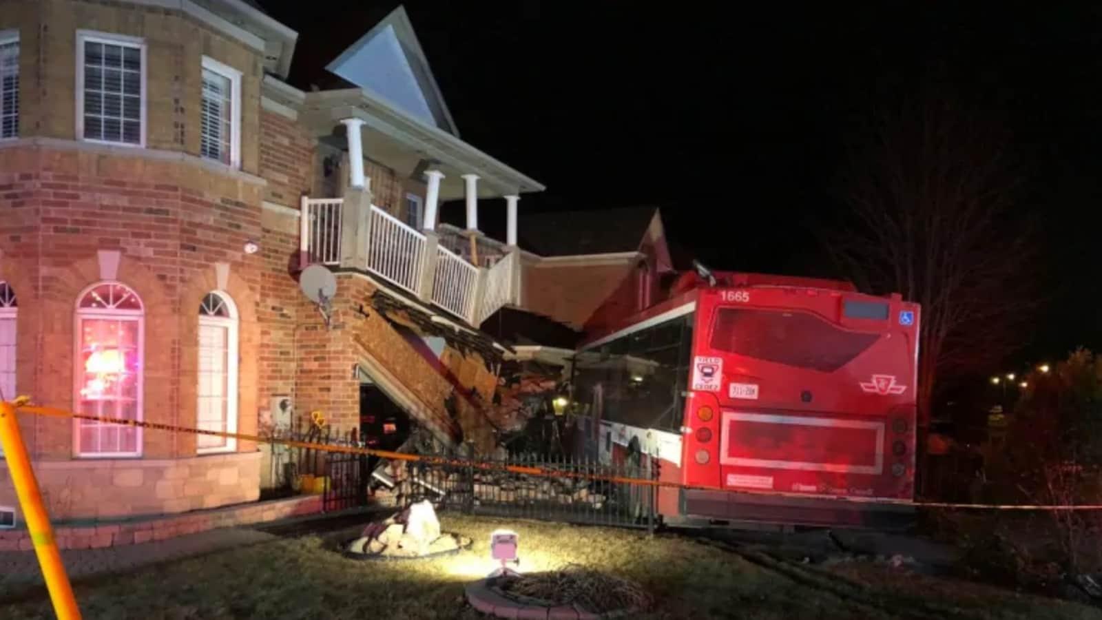 Photo d'un autobus rouge et blanc qui a embouti une partie de la façade d'une maison.