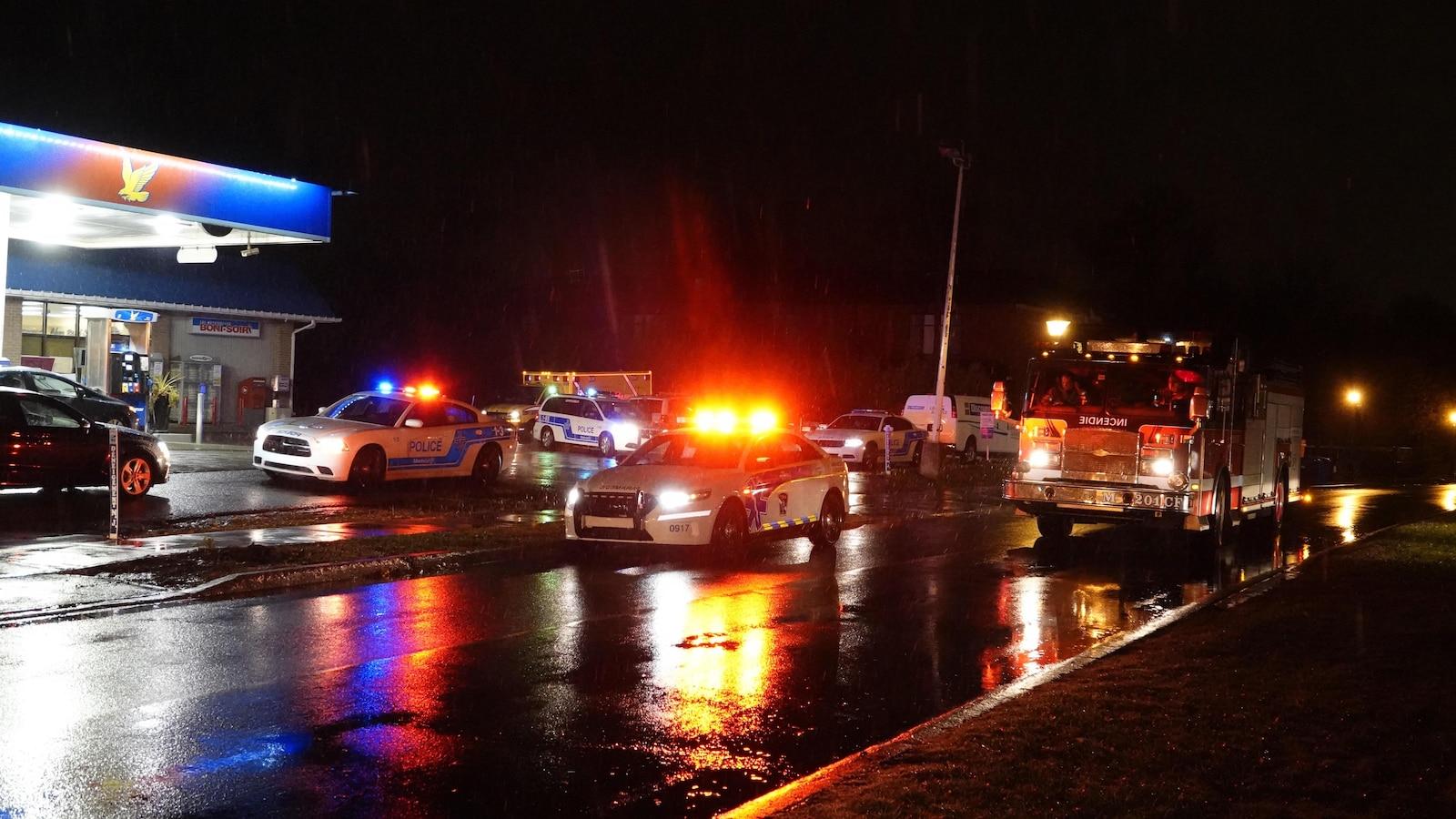Des véhicules de police et de pompier sont stationnés, gyrophares allumés, près d'une station-service.