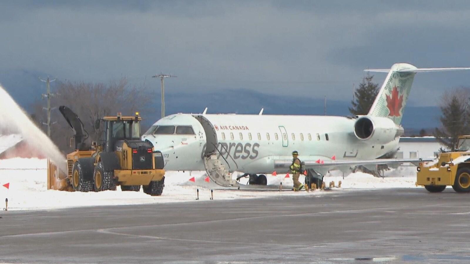 Un pompier inspecte l'avion d'Air Canada qui a sorti de piste.