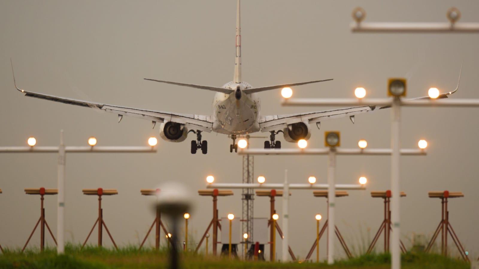 Un avion de ligne s'apprête à atterrir. Il est photographié de derrière.
