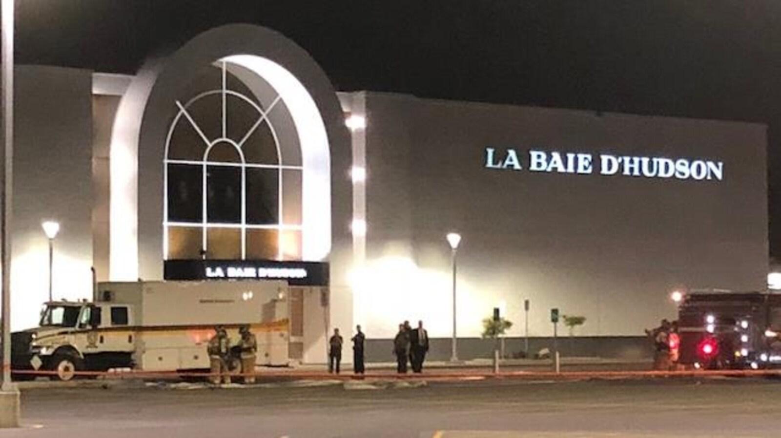 Un camion de la Sûreté du Québec se trouve devant un magasin La Baie.