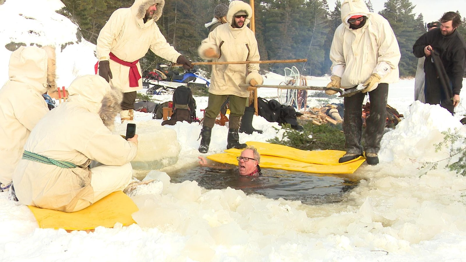 Au milieu d'un trou dans la glace, un homme est dans l'eau jusqu'au cou. À ses côtés, d'autres campeurs bien emmitouflés dans des anoraks se préparent à lui tendre des bâtons pour l'aider à sortir.