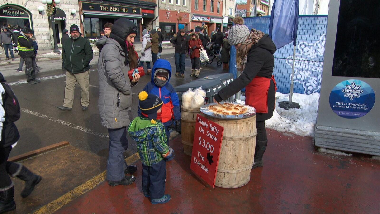Une maman achète de la tire d'érable pour ses deux jeunes garçons.