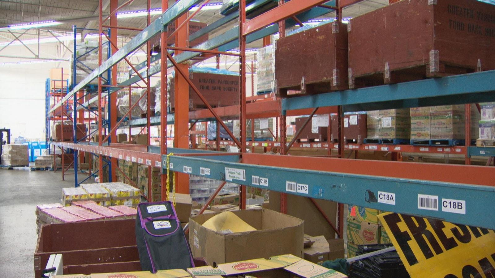 Les étagères d'un entrepôt sont vides sur toute leur longueur.